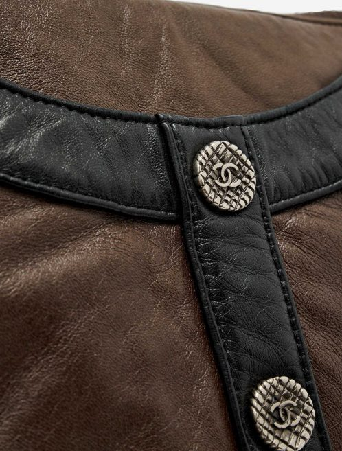 Button detail with Chanel logo of a pre-loved Chanel Girl Medium Lambskin in Brown and Black on SACLÀB