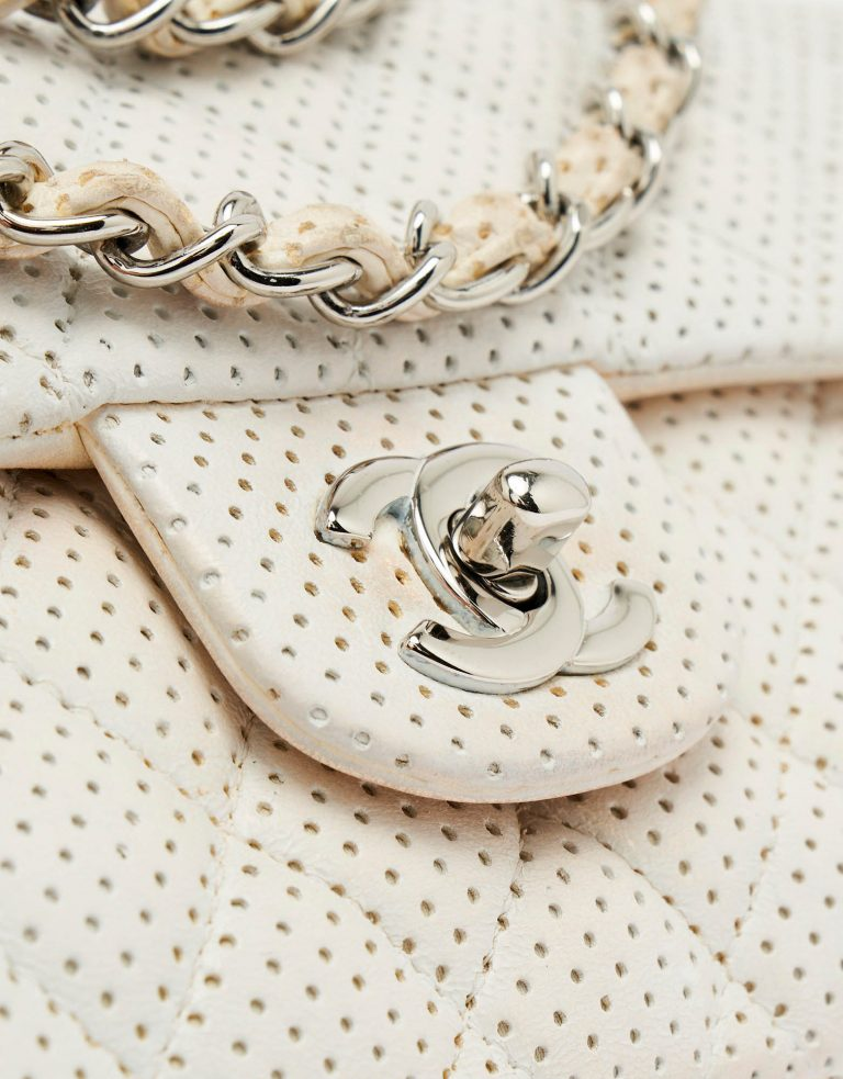 Silver turn-lock detail of a pre-loved Chanel Timeless Baguette Lamb Off White on SACLÀB